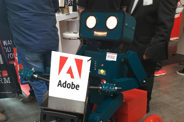 sprechender Roboter Hugo mit Adobe Schild