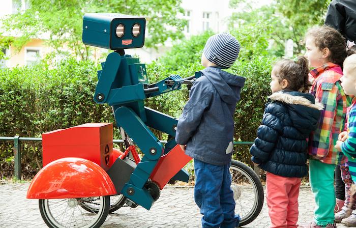 hugo-der-sprechende-Roboter-auf-rotem-Fahrrad-mit-kindern