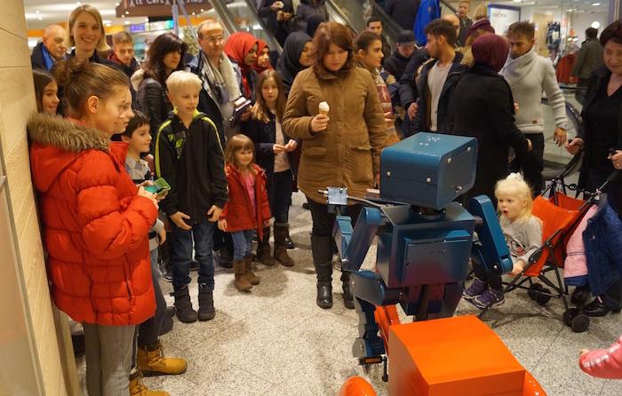 Roboter Dreirad rot Center Weserpark Bremen viele Leute Walk Act