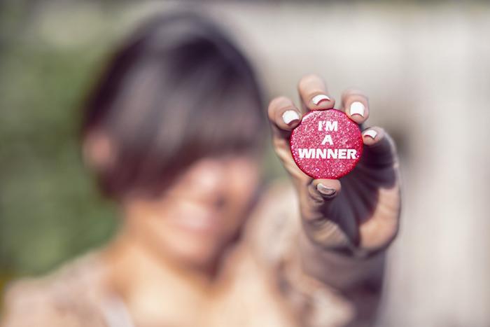Im a Winner Frau hält button