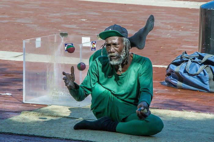 grüner alter Künstler Bein über kopf jonglieren mit bällen