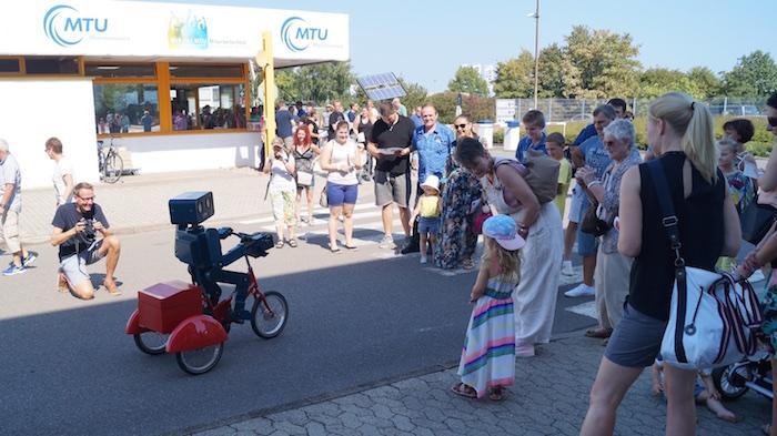 Idee Mitarbeiterfest sprechender Roboter Hugo auf Fahrrad Eingang Begrüßung