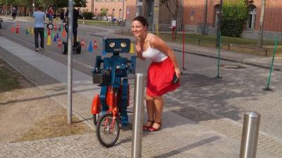 Mitarbeiterfest Charite Berlin Hugo der sprechende Roboter mit Fahrrad junge frau roter rock